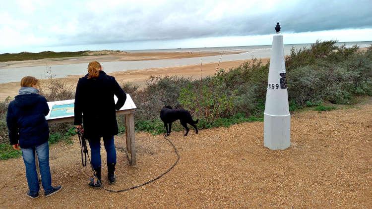 De laatste grenspaal met op de achtergrond de monding van het Zwin en de Noordzee