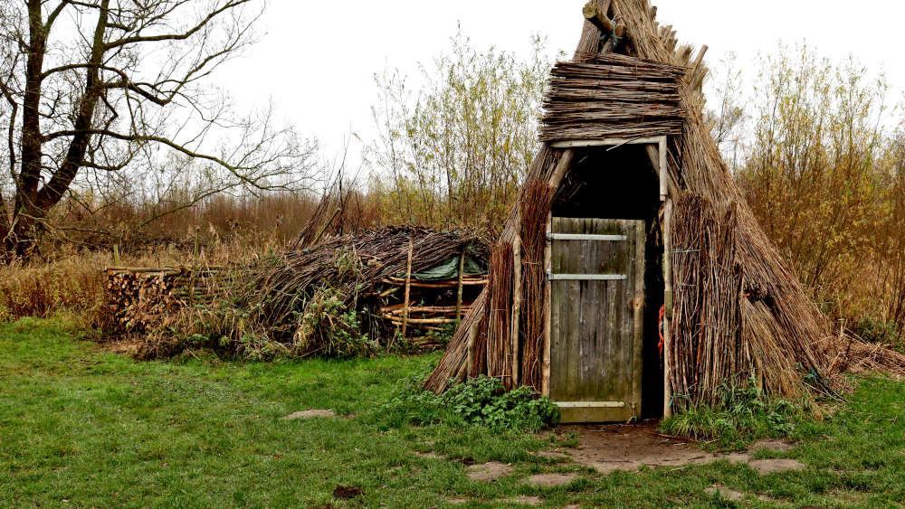 Hut van riet en wilgentakken in het gras bij het Biesbosch Museum