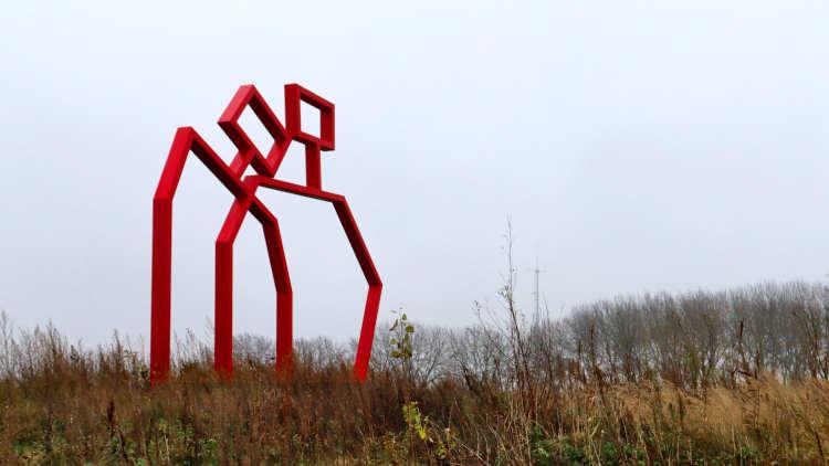 Kunstwerk van rode metalen latten uitbeeldend twee personen.